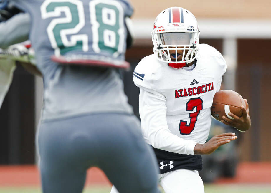 Atascocita quarterback Niyl Campbell carries the ball and is tackled after a short gain in the Class 6A bi-district playoff football game, Saturday, November 15, 2014, at Leonard George Stadium in Spring.