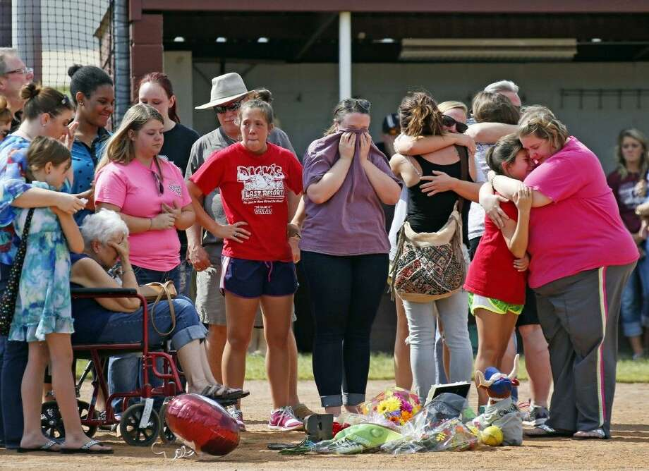 Family and friends mourn at a vigil held for former Wylie High School softball player Meagan Richardson, 19, at the Wylie High School softball field on Saturday, Sept. 27, 2014, in Wylie, Texas. Richardson was one of the four people killed in a bus crash on Friday night in Oklahoma involving the North Central Texas College softball team. Photo: Louis DeLuca