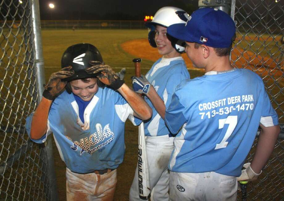 With half the infield dirt on his arms, jersey and pants, Graycen Adrian comes into the Royals dugout after stealing home, his fourth theft of the night during the team's 10-0 City Championship victory. Tyler Saunders (7) and a teammate welcome him in. Photo: Robert Avery