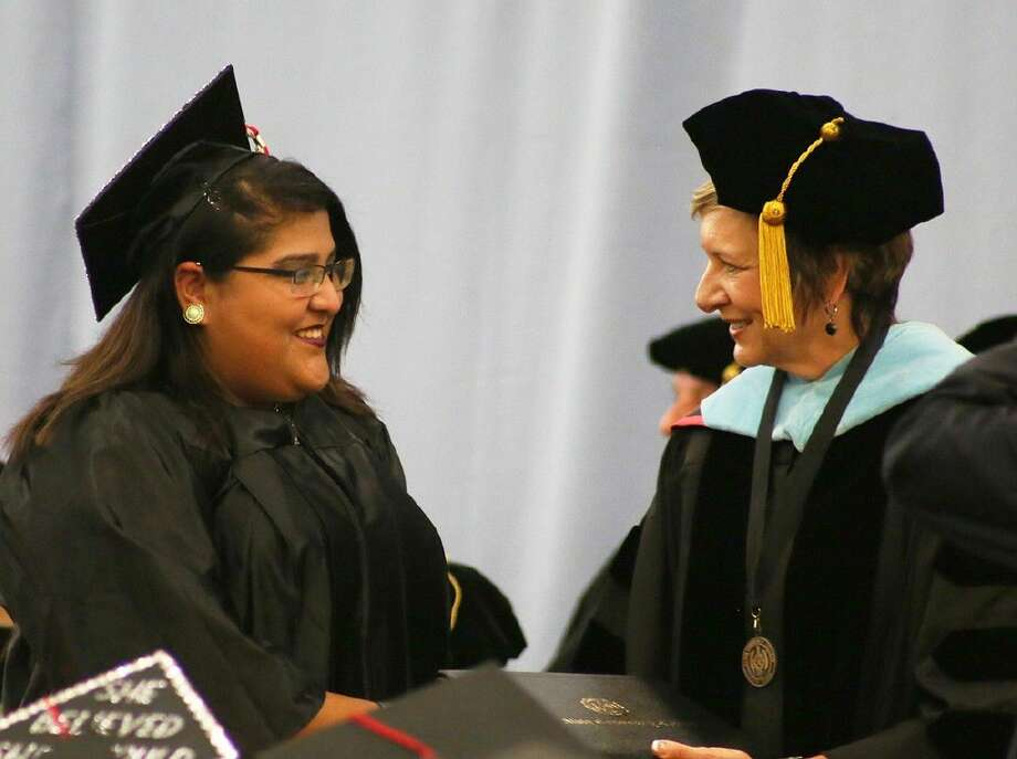 ACC President Dr. Christal M. Albrecht, right, delivers a diploma to graduate Lilia Calvo, of Alvin, during Commencement on May 14.