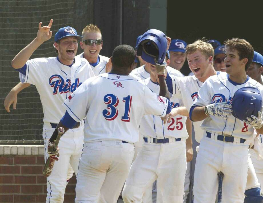 Oak Ridge players celebrate with Justin Alphonse after hitting a solo home run during the fifth inning of a Region II-6A bi-district playoff game Saturday in Oak Ridge. Go to HCNpics.com to purchase this photos and others like it.