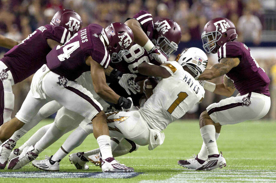 Texas A&M defensive linemen Kingsley Keke and the rest of the Aggie defense tackle Arizona State University running back De'Chavon Hayes during the second quarter of an NCAA college football game at NRG Stadium Saturday September. Photo: Jason Fochtman