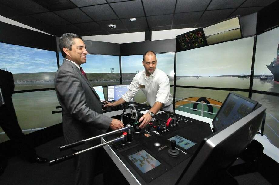 Mr. Andres Alcantar, Texas Workforce Commission chairman and commissioner representing the public, tours the San Jacinto College maritime training center's interactive bridge simulators. San Jacinto College maritime instructor, Clay Buckley, assists. Photo credit: Jeannie Peng-Armao, San Jacinto College marketing, public relations, and government affairs department.