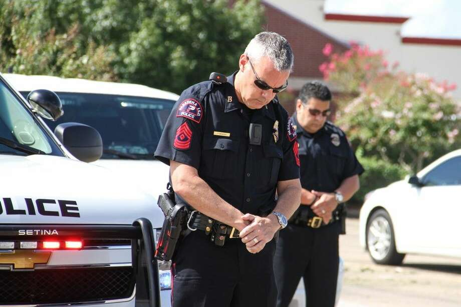 Pasadena ISD Police Sergeant Trae Morris and Captain David Garza observe a moment of silence in honor of Deputy Darren Goforth.