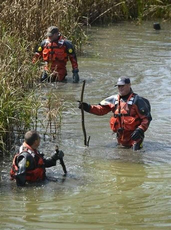 Chicago Police Marine Unit divers search a lagoon at Garfield Park, Sunday in Chicago, after a toddler's decomposed feet and hand were found on Saturday. Photo: Paul Beaty