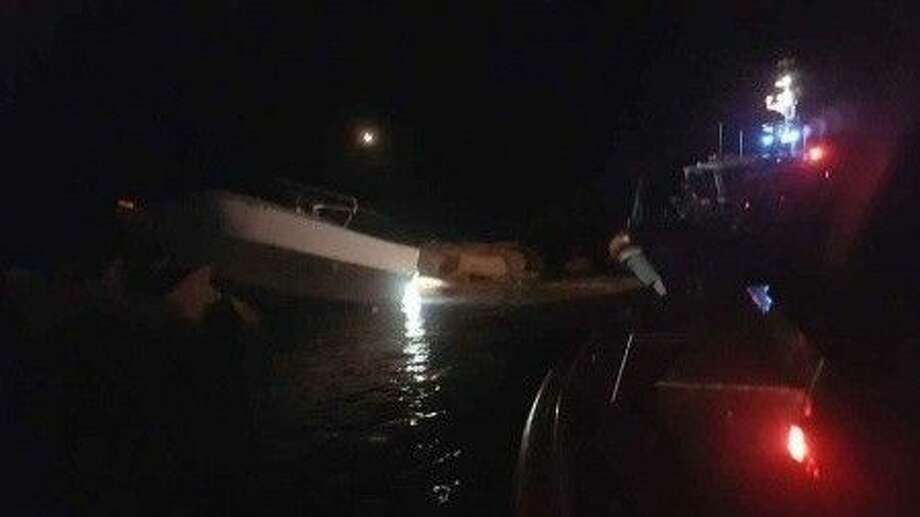 Photos of an aground boat on the Galveston North Jetty and Air Station Houston hoisting injured men to safety. U.S. Coast Guard photos.