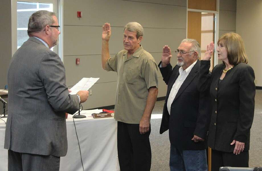County Judge Matt Sebesta, left, administers the oath of office for three regents starting from center: Andy Tacquard, Roger Stuksa and Dr. Patty Hertenberger.