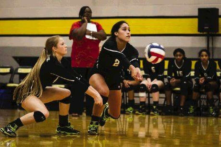 Conroe's Jules Vitela goes for the dig as teammate Blakelea Nettles looks on in a high school volleyball match against Atascocita. Conroe won in five sets. Photo: Michael Minasi