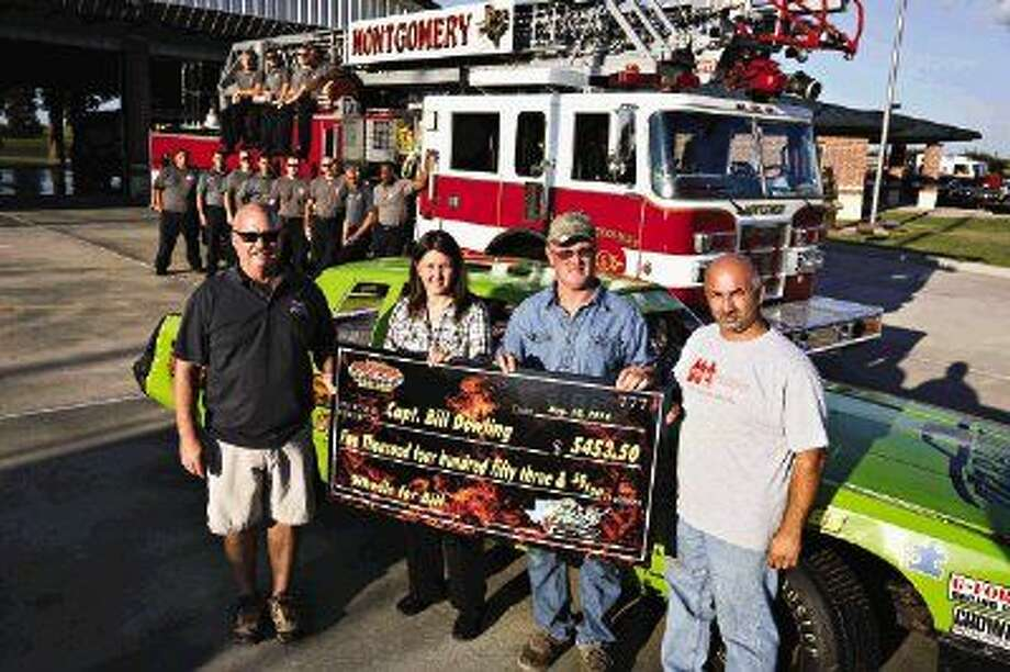Al Goebel, Vice President of Firefighters Helping Firefighters, left, accepts a check on behalf of injured Houston firefighter Capt. Bill Dowling from Gator Motorplex owners Theresa and Randy Wallers, center, and Arthur Hermiz, Gator Motorplex track photographer, right, on Monday at Montgomery Fire Station. Photo: Michael Minasi