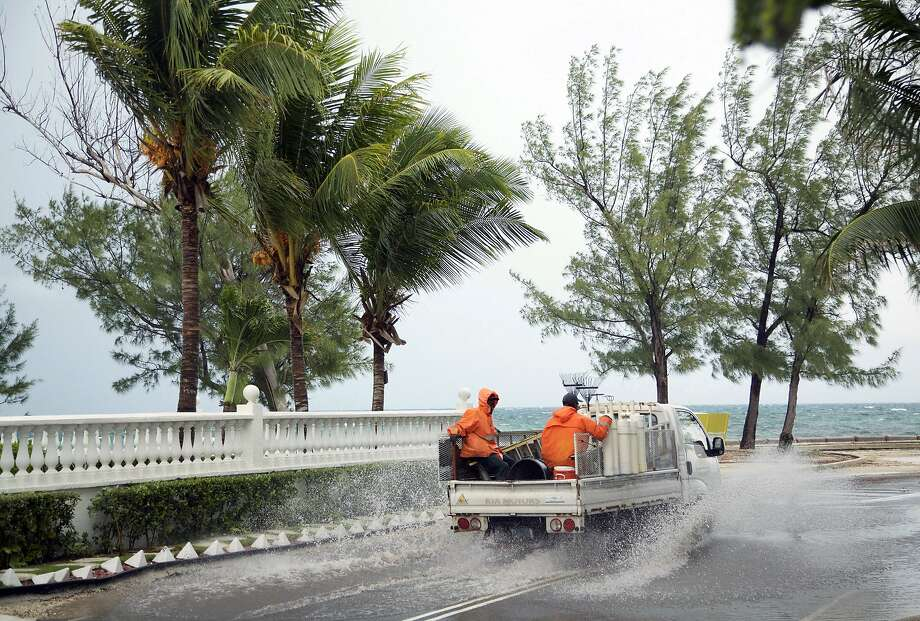 Landscapers ride in a truck along a stretch of road that's partially flooded from rain triggered by the arrival of Hurricane Matthew in Nassau, Bahamas. Photo: Craig Lenihan, Associated Press