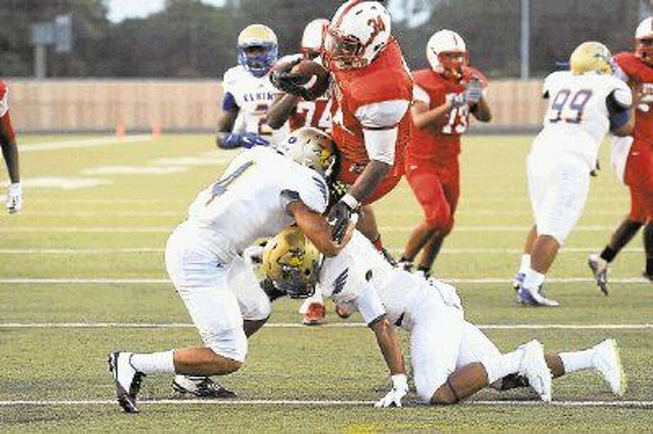 Bellaire running back Trevian Palmer slams into a pair of Elkins defenders during the teams' recent game at Butler Stadium. The Cardinals will close out the non-district portion of their schedule 7 p.m. Thursday night in Spring when they play Klein Collins at Klein Memorial Stadium. Photo: Craig Moseley