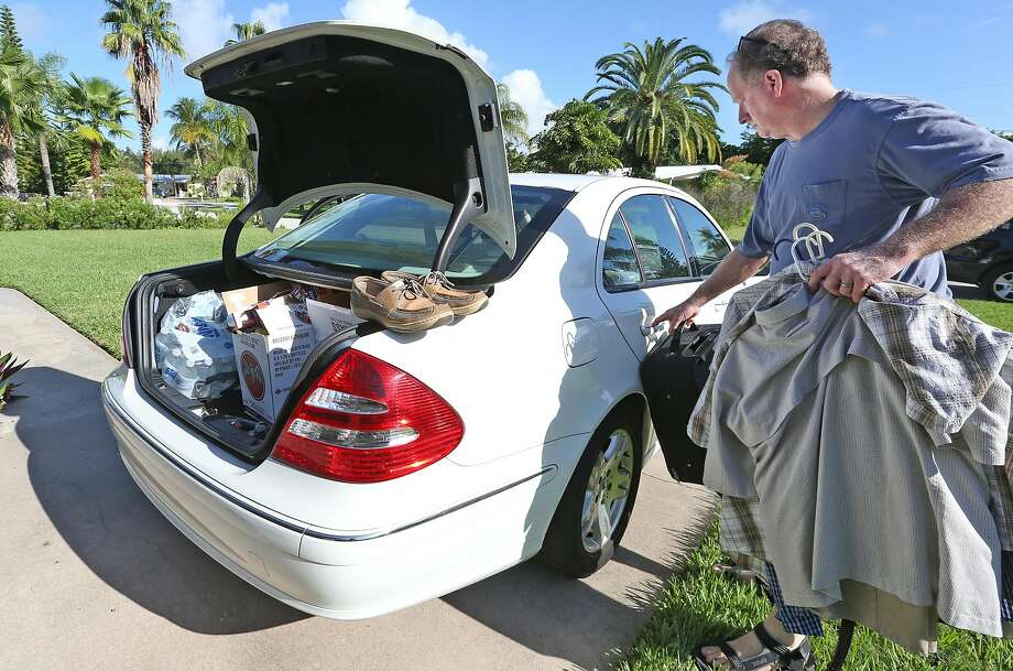 "Joe Roth, 53, of Cocoa Beach, Fla., packs his family's car as he and his wife, Debi, prepare to evacuate as Hurricane Matthew nears. ""I know when they tell you to get out, you go,"" Roth said. Photo: Red Huber, TNS"