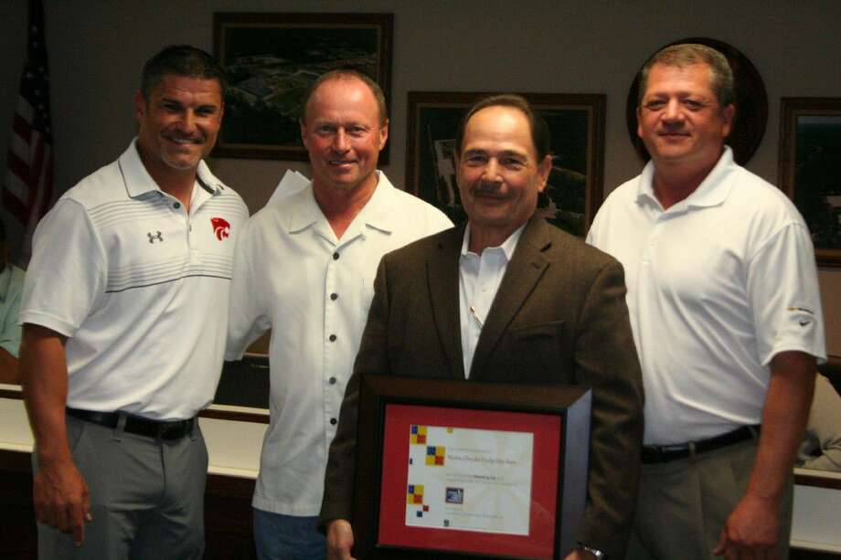 Mike McClennan, Joe Salas and Tom Broadway were presented with a plaque by Splendora High School coach Marcus Schulz to display at their business honoring them for their support of public schools.