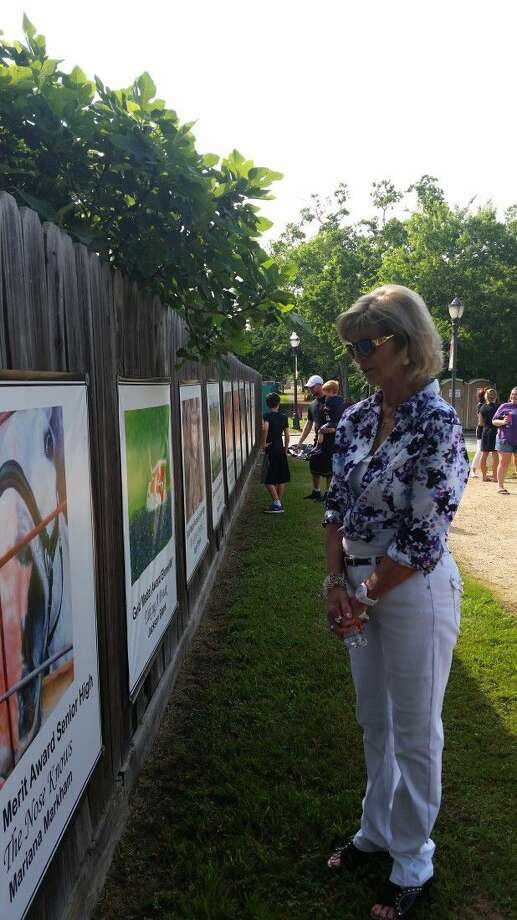 Sandy Williams views award-winning art by Magnolia ISD Students at the May 14 installation of Houston Livestock Show & Rodeo Art on the Cecil Bell Jr. Wall of Fame, on The Stroll in Magnolia. Photo: Submitted