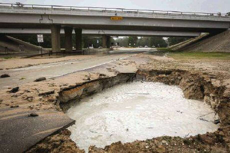 Parts of Grogan's Mill Road and a section of ground collapsed early Tuesday morning after a water transmission line in The Woodlands failed near Woodlands Parkway.