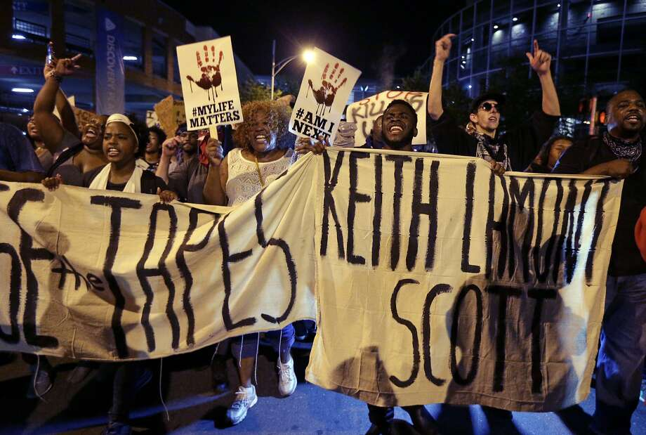 Protesters march last month in Charlotte after the shooting of Keith Lamont Scott. Some experts say a brain injury from a motorcycle wreck could have contributed to the situation. Photo: Chuck Burton, Associated Press
