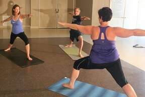 """Yoga participants display the """"Warrior Two"""" pose in City of Friendswood Adult Fitness classes."""