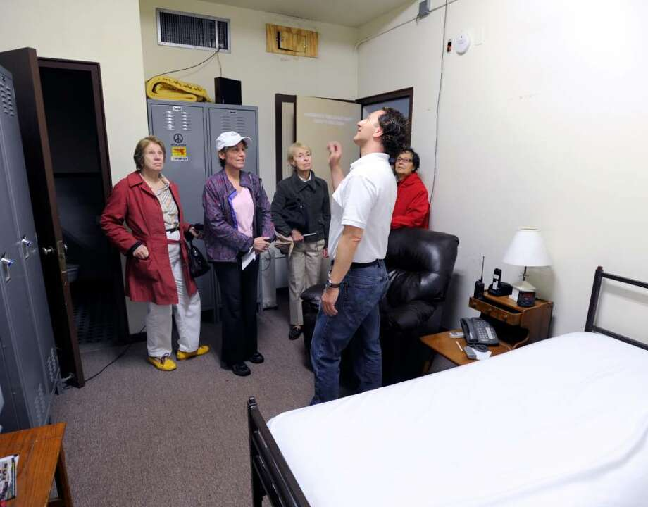 Richard Neuman, foreground, an assistant chief of the Amogerone Volunteer Fire Company and an Representative Town Meeting member for District 11, gives a tour of a spartan sleeping quarter at the Central Greenwich Fire Station to fellow RTM members, Saturday morning, May 8, 2010.  The fellow RTM members are, left to right, Valerie Stauffer - District 7, Rosalind Nicastro - District 11, Katherine Prokop - district 11, and Despina Fassuliotis also of District 11.  The RTM will be voting Monday on whether to allot budget money for building a new headquarters. Photo: Bob Luckey / Greenwich Time