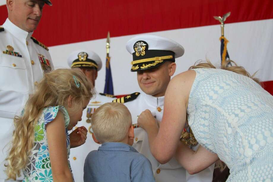Navy Cmdr. Ben Finney receives his command button from his family before assuming command of Navy Recruiting District (NRD) Houston from Navy Cmdr. Rick Evangelista during a change of command ceremony May, 7. NRD Houston consists of integrity-based leadership focused on spirited teamwork and a standing commitment toward excellence. (U.S. Navy photo by Chief Career Counselor Juan Lamoglia Chin-Chilla/RELEASED). Photo: MC1(SW/AW/SCW) Chris Fahey