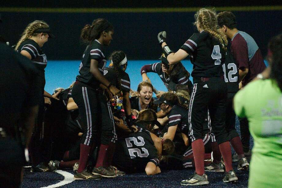 Pearland softball players jump into a pile in the infield after taking a dramatic 8-7 win over Katy Seven Lakes in the finale of a best-of-three series in Sweeny Friday night. Photo: Kirk Sides