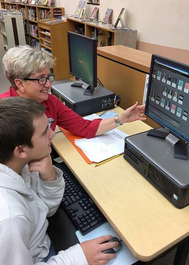 Pearland Junior High South teacher Tina Laningham assists Tait Daniel with online ancestry research.