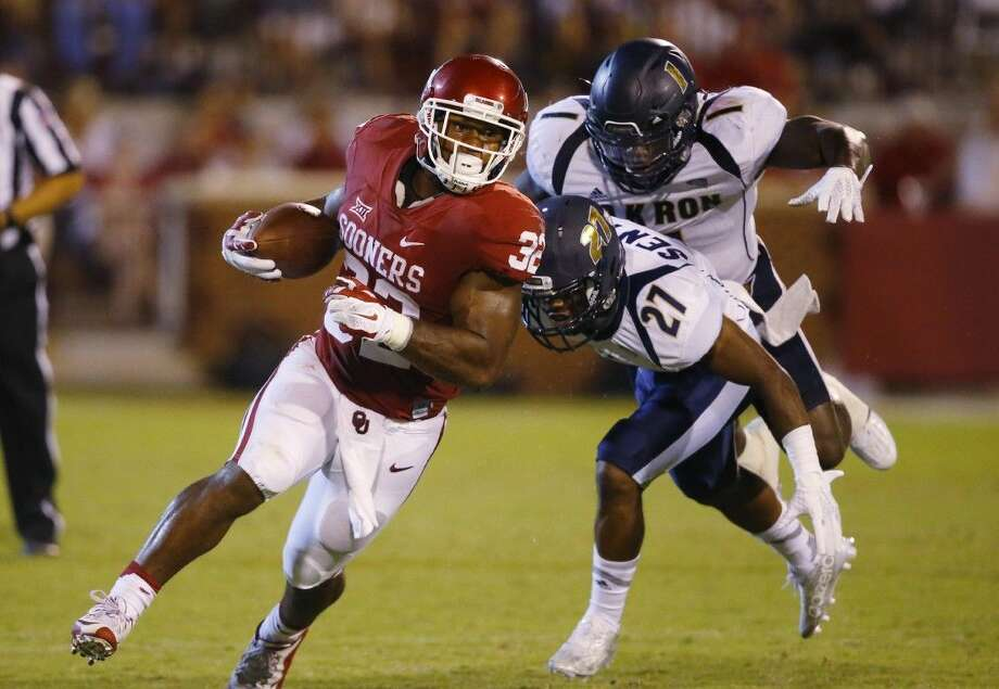 In this Sept. 5, 2015, file photo, Oklahoma running back Samaje Perine (32) carries past Akron cornerback John Senter (27) in the third quarter of an NCAA college football game in Norman, Okla. Amid the video game-like passing numbers seen across college football in recent years, rushing numbers are at their highest totals in more than three decades.