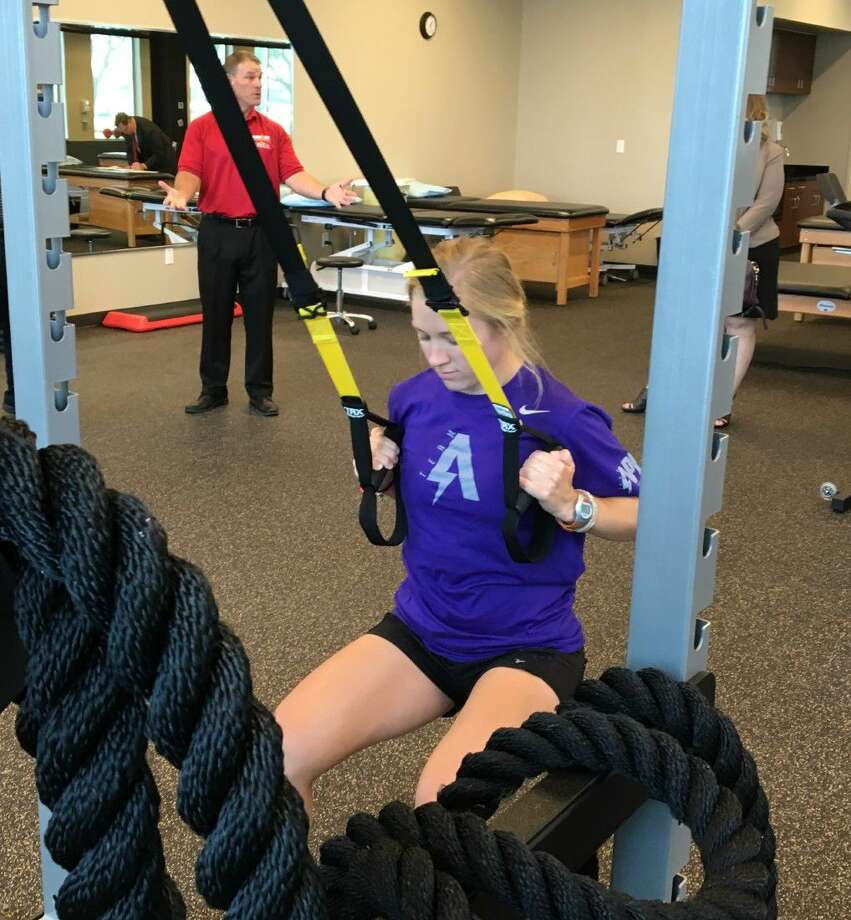 PT Tech Courtney Dunstan demonstrates how to perform one of the exercises at the Memorial Hermann IRONMAN Sports Medicine Institute at Sugar Land. The facility will provide a multitude of ways for MHSL to get athletes of all ages back in the game.