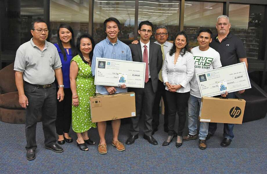 Cypress Falls seniors Viet Nguyen and Michael Gil are joined by their families as they accept Darren Goforth Memorial Scholarships from Robert Partin, far right, through the SG Adopt a School program.