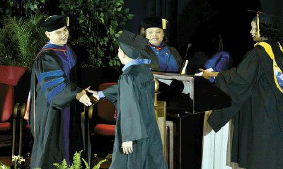 Lone Star College awarded a record 7,032 associate degrees and certificates during its recent graduation ceremonies. Pictured (left to right) are Dr. Gerald Napoles, LSC-North Harris president, a LSC student, Dr. Valschkia Dabney, vice president, Centers and Carolyn Wade, interim vice president, Student Services.