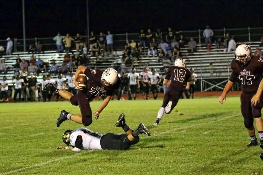 Anahuac's Cesar Molina breaks through the Longhorn defense to flip Zach Clifton (20) for a loss, Sept. 11, 2015. Photo: Sean Ashley Jones