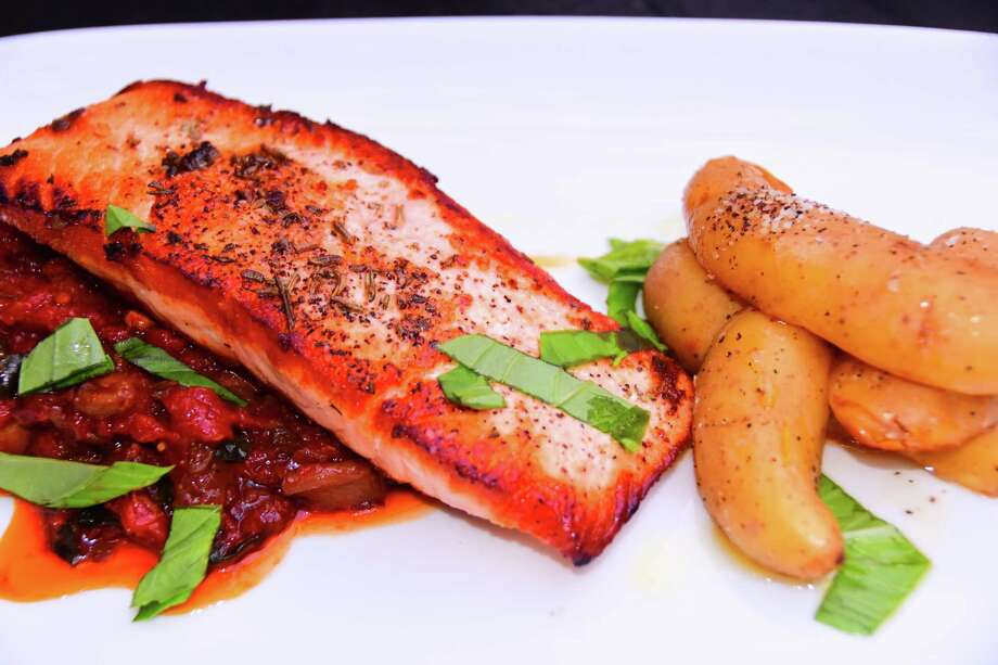 The salmon entrée on the new menu at The Olde English in Albany is served with fingerling potato, wild mushroom with tomato and a garnish of basil. (Steve Barnes/Times Union)