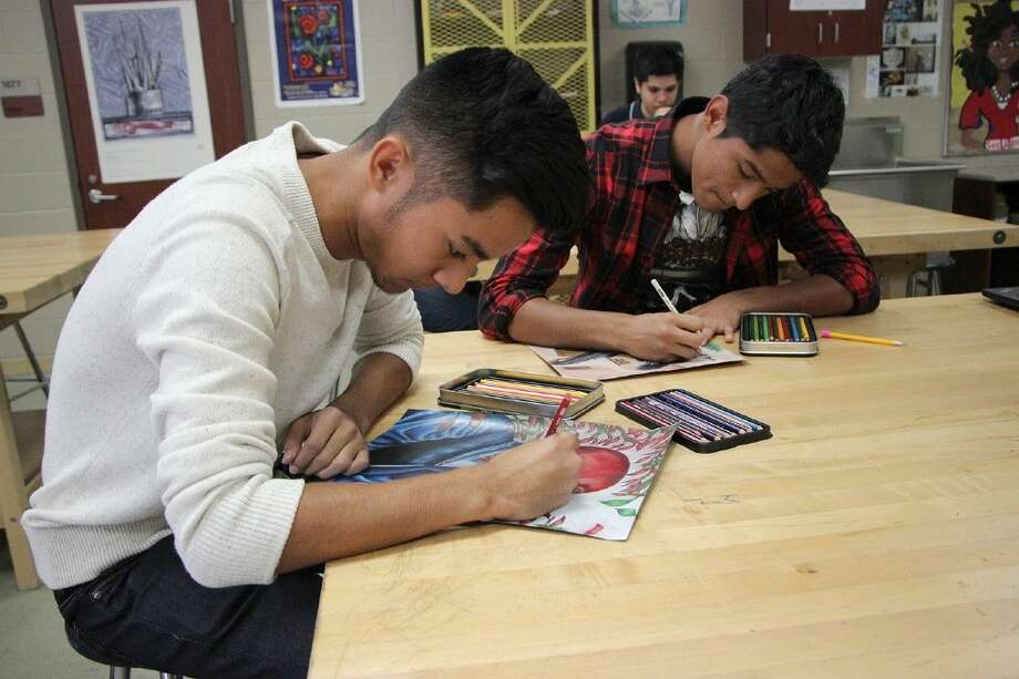 In preparation for the Nov. 1 Dia De Los Muertos student art exhibit at the Lawndale Art Center, Cypress Lakes junior Victor Mendoza finishes coloring in his art work. Photo: Briana Ossege