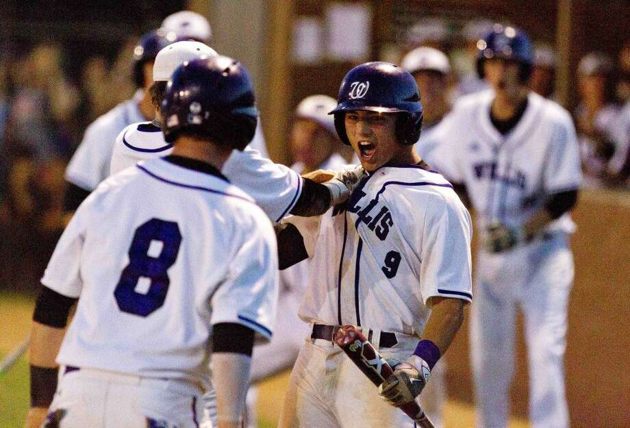 Willis' Corbin Marett , right, celebrates after a 2-RBI double by Trevor Summers during the fourth inning of a area playoff game Wednesday in Willis. Go to HCNpics.com to purchase this photo and others like it.