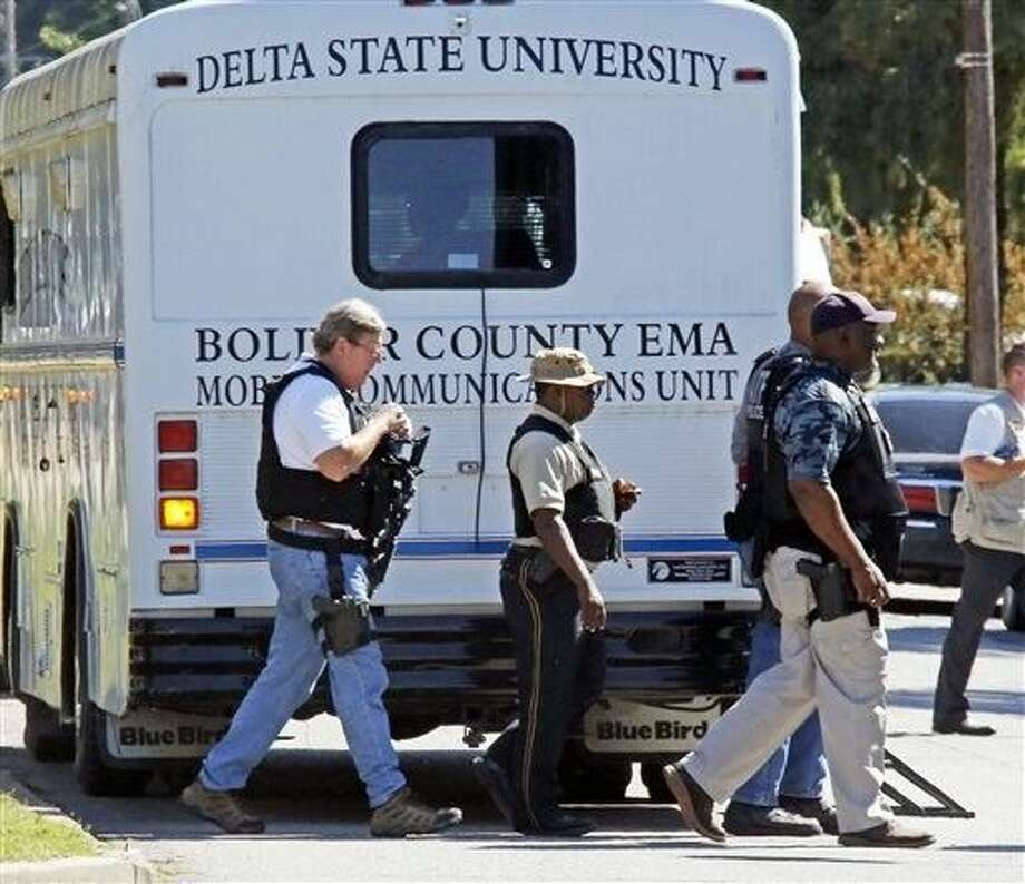 Law enforcement walk across the Delta State University campus to search for an active shooter in connection with the shooting of history professor Ethan Schmidt in his office at Delta State University in Cleveland, Miss., Monday. Photo: Rogelio V. Solis