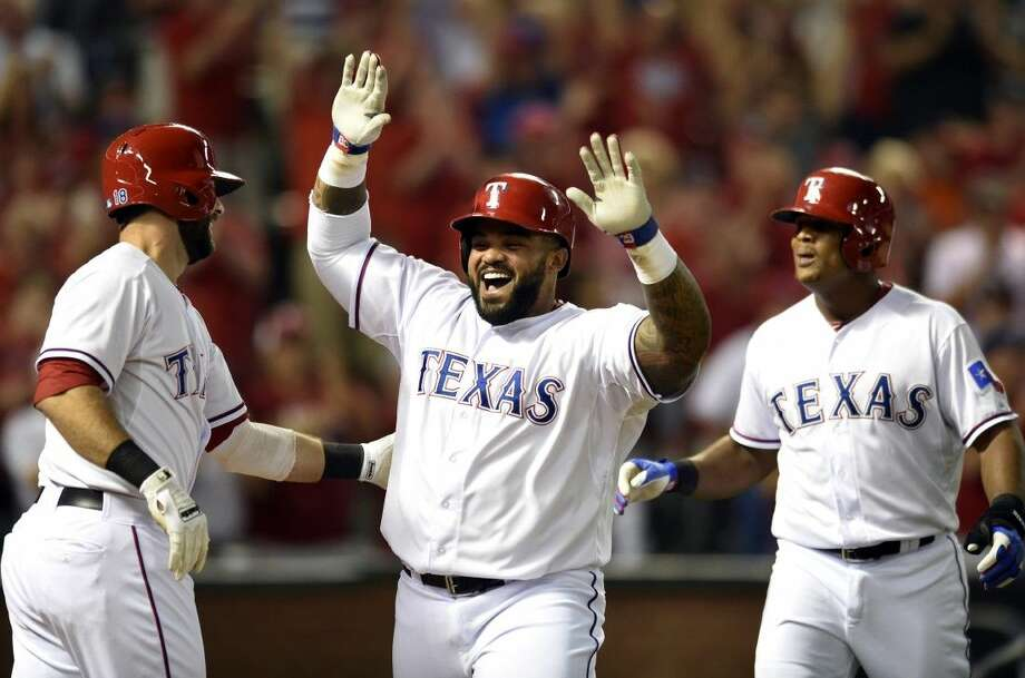 The Rangers' Prince Fielder, center, is congratulated by teammates Mitch Moreland, left, and Adrian Beltre after his two-run home run in the eighth inning.