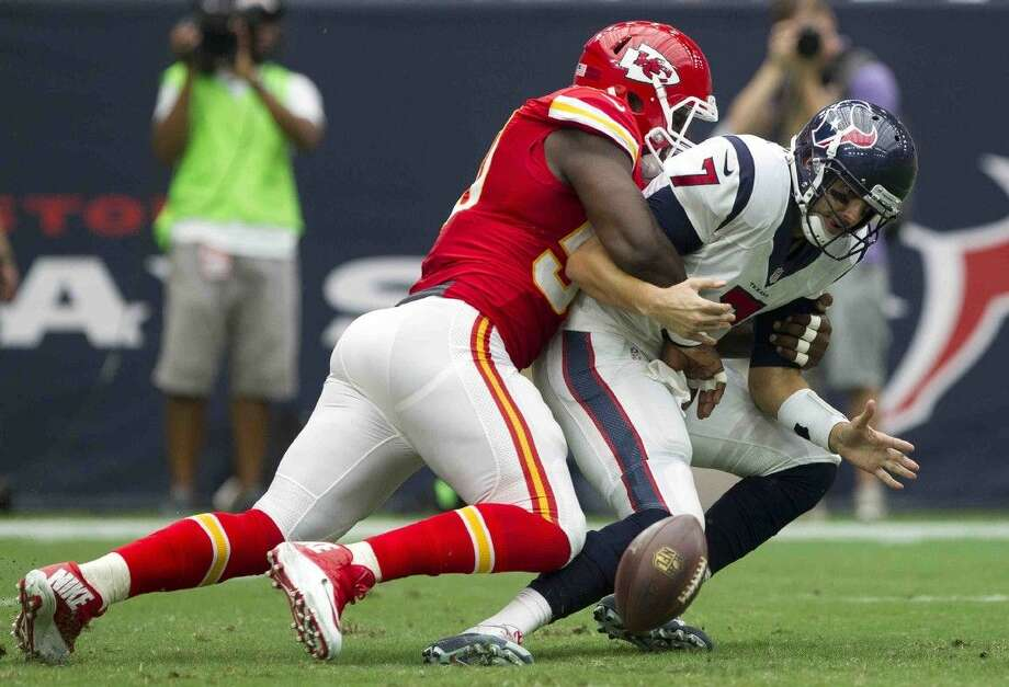 Chiefs linebacker Justin Houston strip sacks Texans quarterback Brian Hoyer on Sunday. Texans coach Bill O'Brien hasn't decided whether to start Hoyer or Ryan Mallett on Sunday against the Panthers.