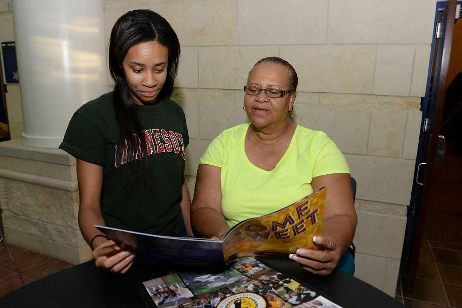 Cypress Falls High School junior Alexius Green and her mother, Caneke Johnson, look through a Louisiana State University college brochure they received during the 20th annual College Night in 2014.