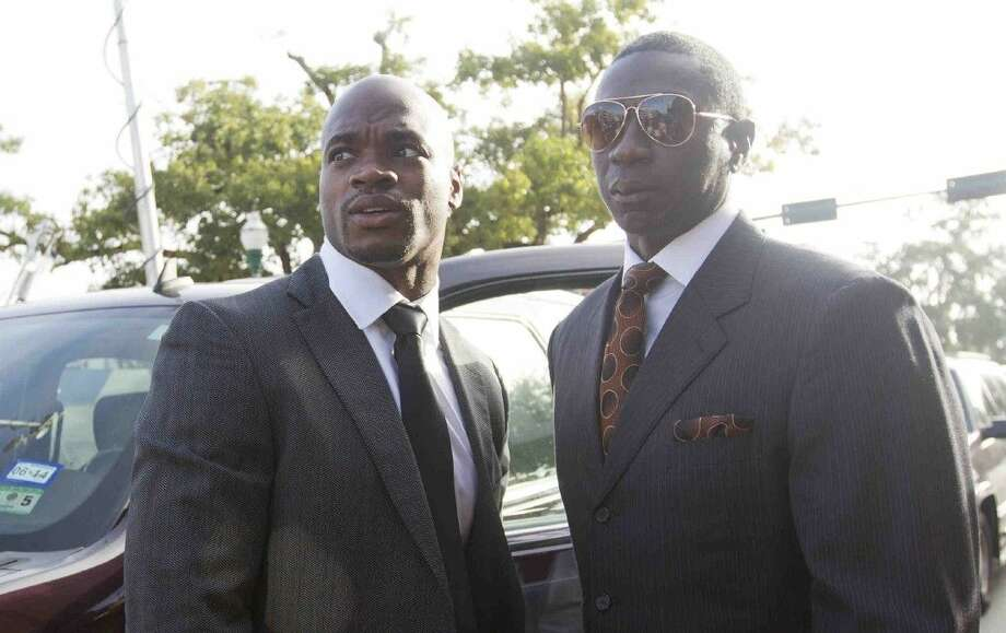 Minnesota Vikings running back Adrian Peterson, left, is seen in front of the Lee G. Alworth Building Wednesday, Oct. 8, 2014, in Conroe, Texas. Peterson made his first appearance at Montgomery County's 9th state District Court for a child abuse charge stemming from an incident where he used a switch to discipline his four-year-old son at his Montgomery County home earlier this year.