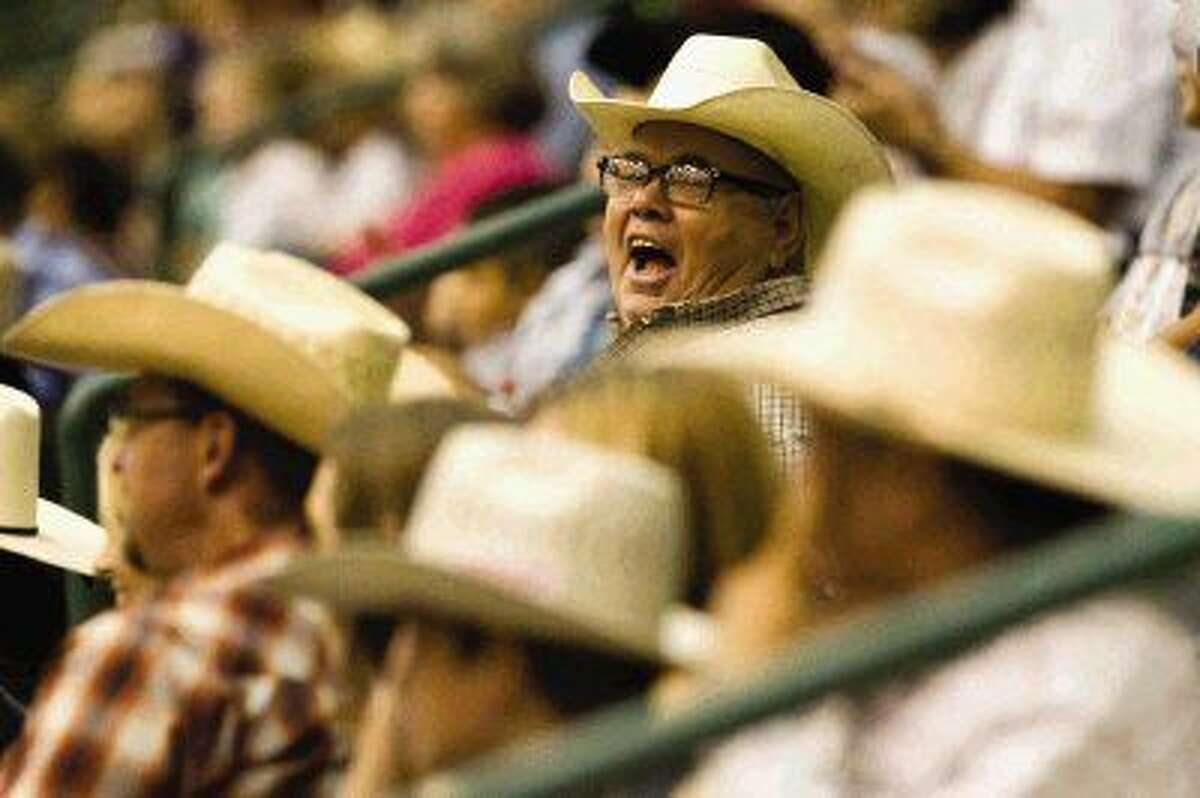 Kelly Woodrome laughs at a rodeo clown's joke between sessions during the Champion Bull Riding at Conroe Bull Mania at the Lone Star Expo Center Saturday. Go to HCNpics.com to view more photos from the event.