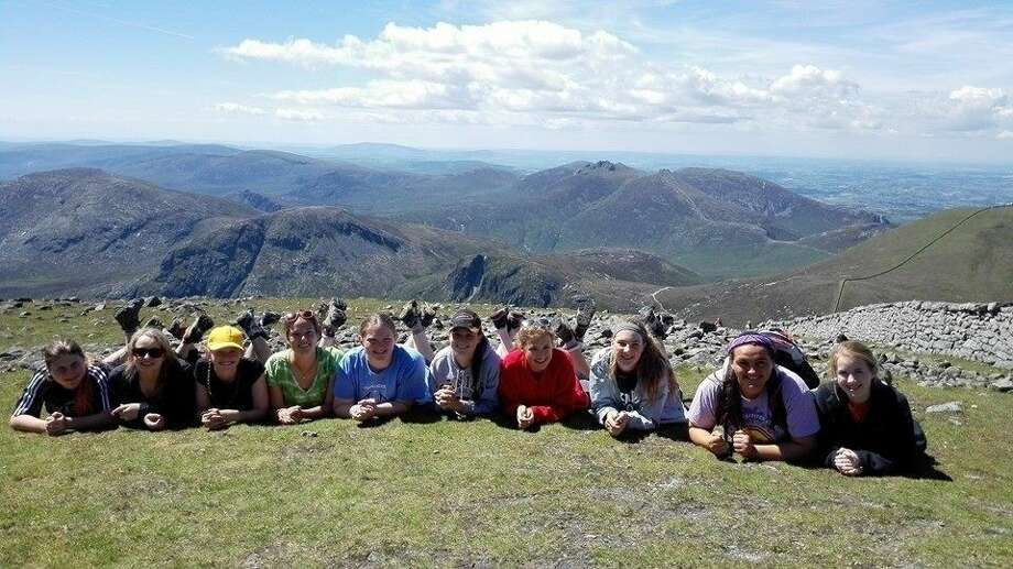 Girl Scouts pose with a mountain landscape on their trip to Ireland over the summer.