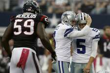 Dallas Cowboys punter Chris Jones, and kicker Dan Bailey (5) celebrate Bailey's field goal in overtime in a 20-17 victory over the Texans. The Texans' Whitney Mercilus is at left.