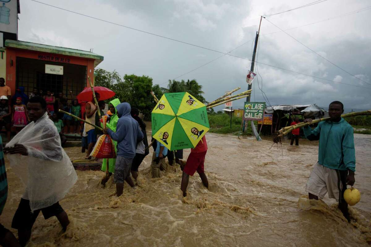 People wade through a street flooded by a nearby river overflowing from the heavy rains caused by Hurricane Matthew, in Leogane, Haiti, Wednesday, Oct. 5.