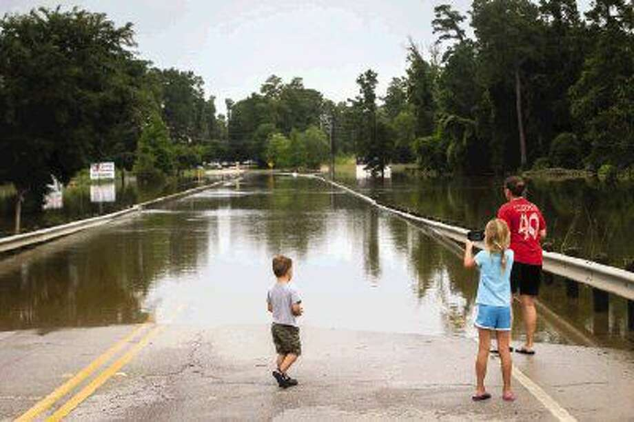 Spring resident Teresa Haynes and her children, Jacob, 3, and Amy, 6, look down a flooded Gosling Road Sunday morning. Photo: Michael Minasi