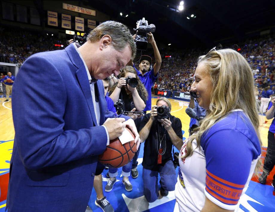 University of Kansas head basketball coach Bill Self writes a $10,000 check to Jordan Stiers after she won a half-court shot contest. Photo: Jeff Jacobsen - Kansas Athletics