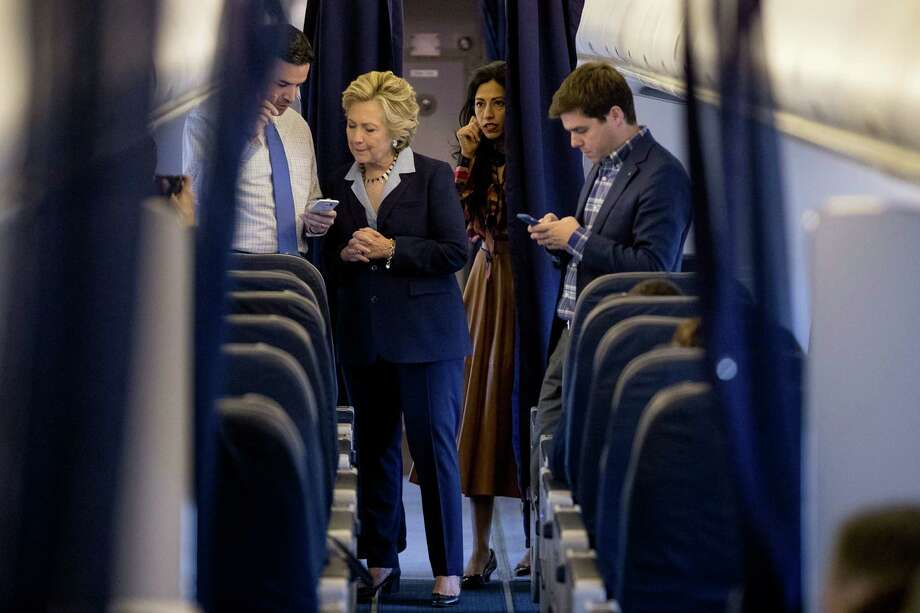 Democratic presidential candidate Hillary Clinton speaks with campaign officials aboard her plane in White Plains, N.Y. Readers share varying opinions about the candidate. Photo: Andrew Harnik /Associated Press / Copyright 2016 The Associated Press. All rights reserved.
