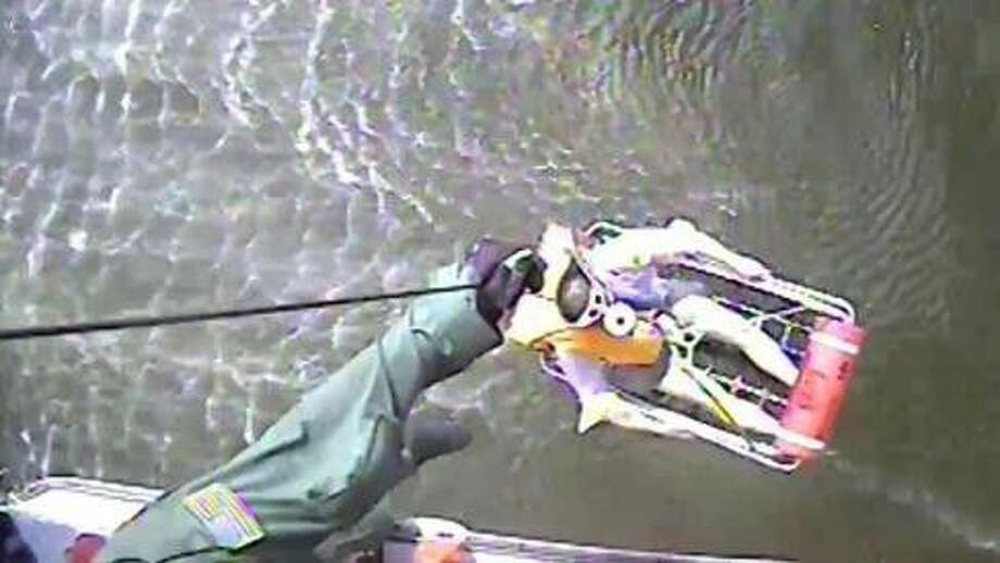 An Air Station Houston helicopter crew drops the rescue swimmer, hoists a man to safety and returns him to the air station to be checked by EMS. U.S. Coast Guard video by Air Station Houston.