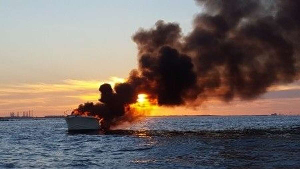 A boat burns near the South Jetty off Galveston at sunset Sept. 19, 2015. U.S. Coast Guard photo by Petty Officer 3rd Class Oliver R. Tallyn.