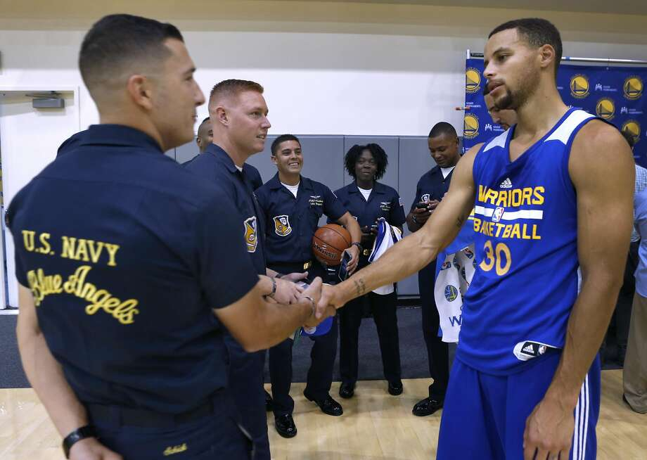 Stephen Curry welcomes members of the Blue Angels' ground crew to the Warriors' practice facility in Oakland on Wednesday. Photo: Paul Chinn, The Chronicle