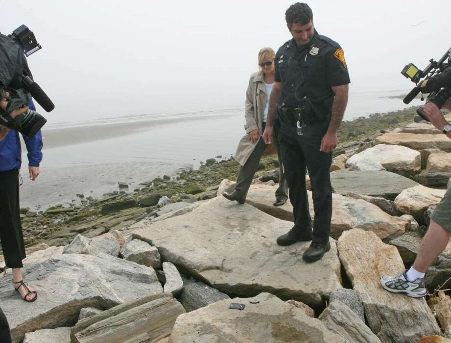 Officer Mark Simonetti, right, and Sergeant  Giselle Duszpoj find a cell phone parts on West Beach jetty at Seaside Park where a man was struck by lighting and killed on Saturday morning, May 8, 2010. Three other men sustained injuries. Photo: B.K. Angeletti / Connecticut Post