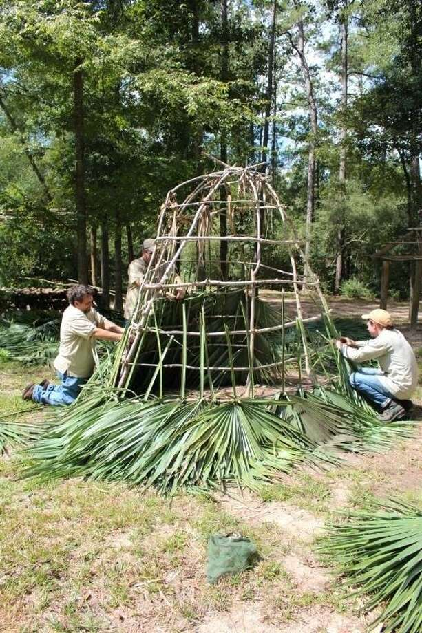 From left to right, Jones Park staff members Lon Goodrum, Monte Parks and Rodger Lee work to re-thatch the Akokisa Indian hut. Photo: Submitted Photo